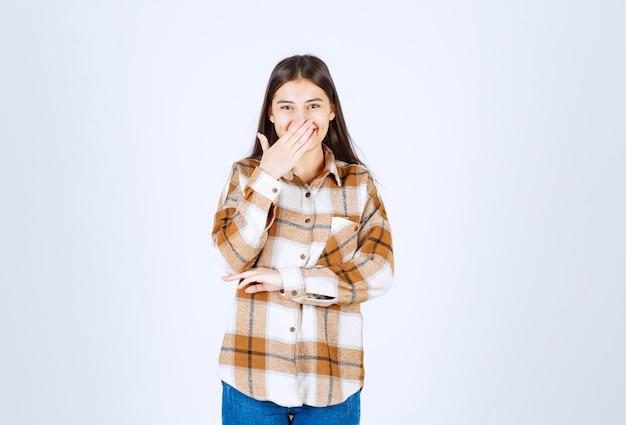 Młoda piękna dziewczyna w stroju casual starając się śmiać się na białej ścianie.