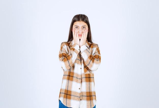 Młoda piękna dziewczyna w stroju casual, trzymając twarz na białej ścianie.