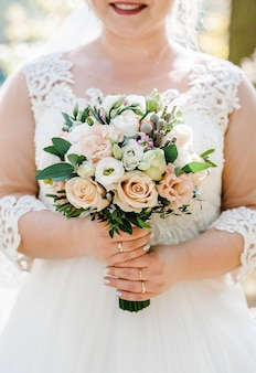 Młoda piękna dziewczyna w sukience stoi i trzyma za rękę bukiet pastelowych różowych kwiatów i zieleni w przyrodzie. panna młoda trzyma na zewnątrz bukiet ślubny.