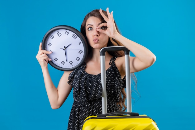 Młoda piękna dziewczyna w sukience w groszki stojąca z walizką trzymająca zegar robi ok znak patrząc na kamery przez ten znak pozytywny i szczęśliwy na niebieskim tle