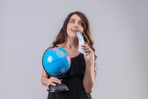 Młoda piękna dziewczyna w sukience w groszki trzyma bilety lotnicze i kula ziemska patrząc na stojąco z marzycielskim spojrzeniem na białym tle