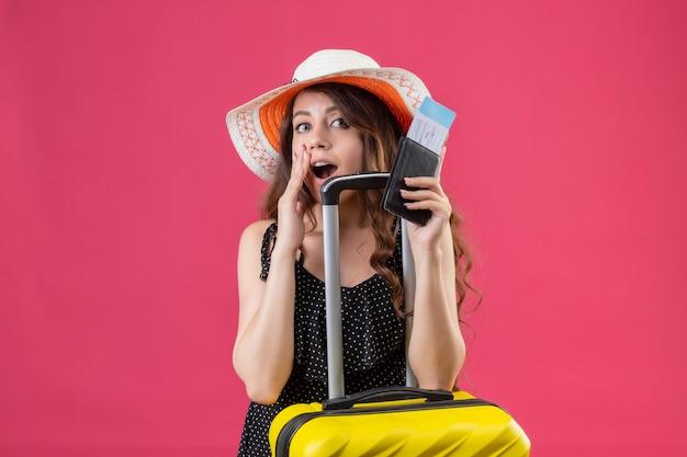 Młoda piękna dziewczyna w sukience w groszki w letnim kapeluszu stojącym z walizką trzymając bilety lotnicze, patrząc zaskoczony i szczęśliwy na różowym tle