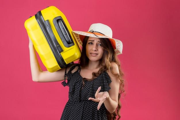Młoda piękna dziewczyna w sukience w groszki w letnim kapeluszu trzyma walizkę patrząc na kamery ze zdezorientowanym wyrazem twarzy, prosząc stojąc na różowym tle