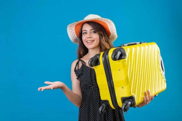Młoda piękna dziewczyna w sukience w groszki w letnim kapeluszu trzyma walizkę uśmiechnięta wesoło patrząc na aparat, przedstawiając ręką stojącą na niebieskim tle