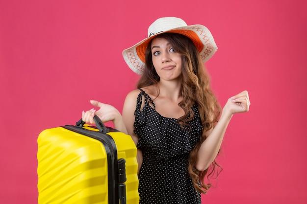 Młoda piękna dziewczyna w sukience w groszki w letnim kapeluszu trzymając walizkę patrząc na kamery z dezorientowanym wyrazem stojącym na różowym tle