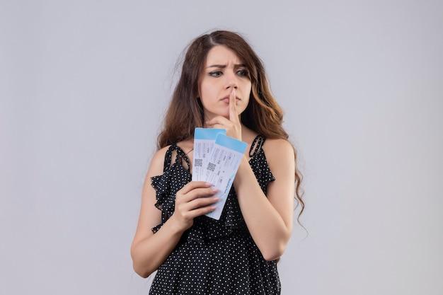 Młoda piękna dziewczyna w sukience w kropki trzyma bilety lotnicze stojąc z zamyślonym wyrazem palcem na ustach, myśląc, mając wątpliwości na białym tle
