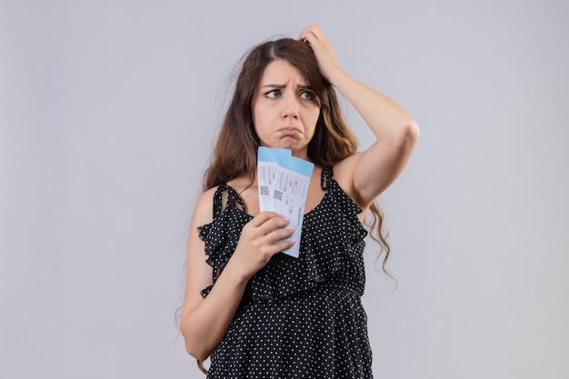 Młoda piękna dziewczyna w sukience w kropki trzymając bilet lotniczy niezadowolony ze smutnym wyrazem twarzy stojącej na białym tle
