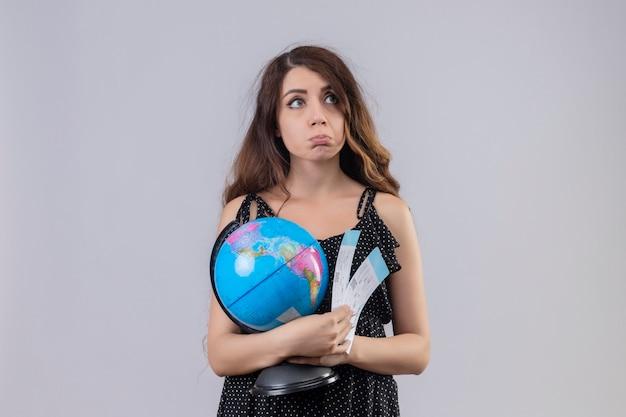 Młoda piękna dziewczyna w sukience w kropki trzymając kulę ziemską i bilety lotnicze stojąc z zamyślonym wyrazem myśli, mając wątpliwości na białym tle