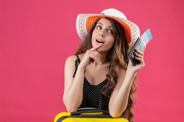 Młoda piękna dziewczyna w sukience w kropki w letnim kapeluszu trzyma bilety lotnicze patrząc z boku z zamyślonym wyrazem myśli pozytywnej pozycji na różowym tle