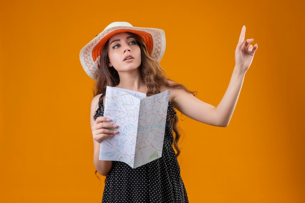 Młoda piękna dziewczyna w sukience w kropki w letnim kapeluszu trzymając mapę gestykuluje poczekaj minutę z poważnym pewnym wyrazem twarzy stojącej na żółtym tle