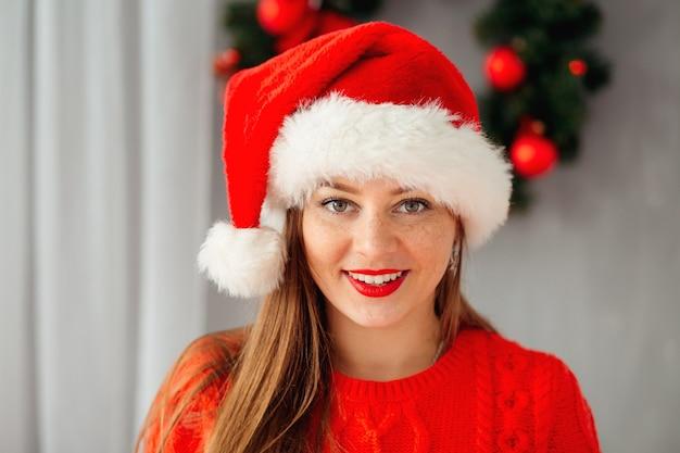 Młoda piękna dziewczyna w świątecznym kapeluszu patrzy na kamerę