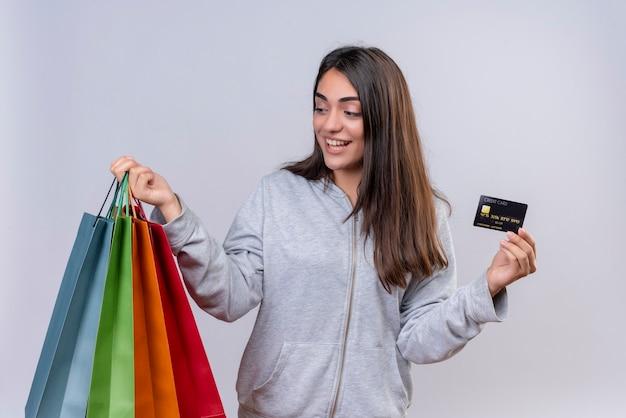 Młoda piękna dziewczyna w szarej bluza z kapturem, patrząc na paczki z uśmiechem na twarzy trzymając paczki i stojącą kartę kredytową na białym tle na białym tle