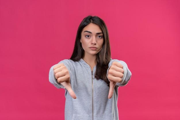 Młoda piękna dziewczyna w szarej bluzie z kapturem nieprzyjemnie patrzy na kamerę na twarzy i robi gest niechęci stojąc na różowym tle