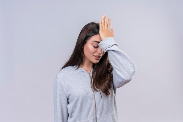 Młoda piękna dziewczyna w szary bluza z kapturem dotykając głowy za błąd patrząc mylić pojęcie złej pamięci stojącej na białym tle