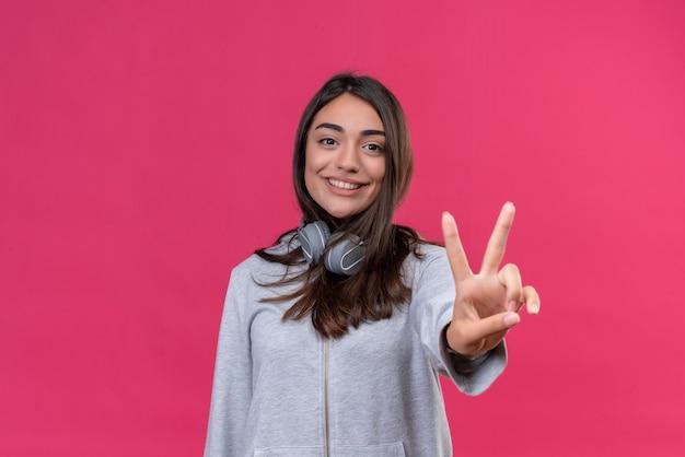 Młoda piękna dziewczyna w szary bluza z kapturem noszenie słuchawek patrząc na aparat uśmiech na twarzy robi gest pokoju stojąc na różowym tle