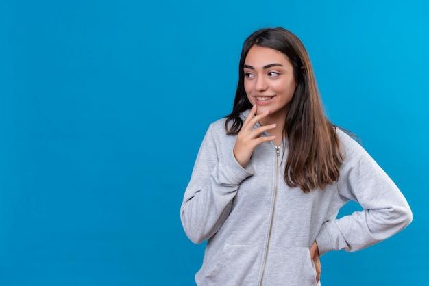 Młoda piękna dziewczyna w szary bluza z kapturem, odwracając wzrok z zamyślonym wyrazem twarzy myślenia stojącego na niebieskim tle