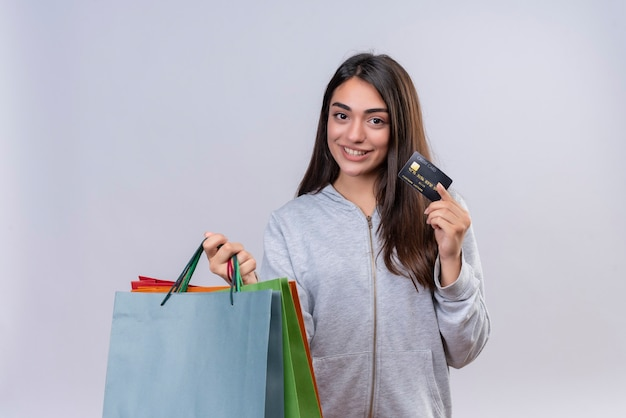 Młoda piękna dziewczyna w szary bluza z kapturem patrząc na kamery z uśmiechem na twarzy trzymając pakiety i zdolność kredytowa na białym tle