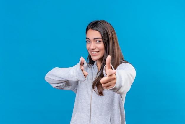 Młoda piękna dziewczyna w szary bluza z kapturem patrząc na kamery z uśmiechem na twarzy, wskazując na aparat stojący na niebieskim tle