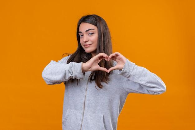 Młoda piękna dziewczyna w szarym kapturem robi romantyczny gest serca patrząc na kamery z uśmiechem na twarzy stojącej na pomarańczowym tle