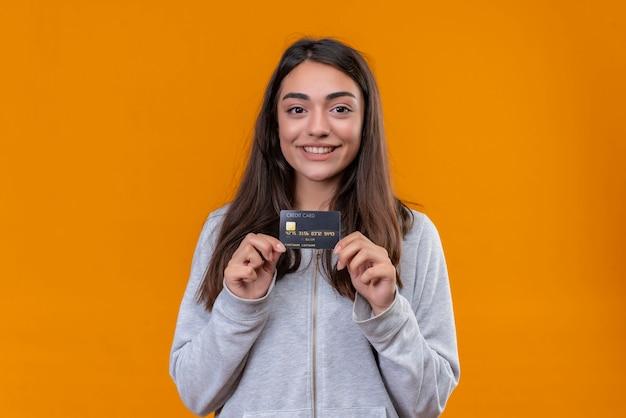 Młoda piękna dziewczyna w szarym kapturem trzyma kartę kredytową i patrząc na kamery z simle na twarzy stojącej na pomarańczowym tle