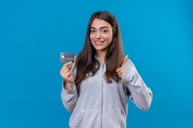 Młoda piękna dziewczyna w szarym kapturem trzyma kartę kredytową i patrząc na kamery z uśmiechem na twarzy i robi jak gest stojąc na niebieskim tle