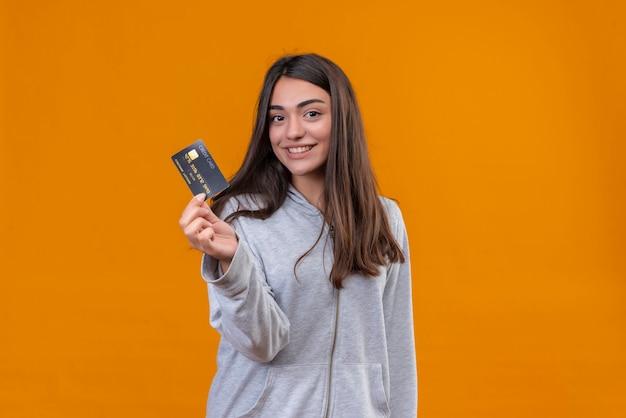 Młoda piękna dziewczyna w szarym kapturem trzyma kartę kredytową i patrząc na kamery z uśmiechem stojąc na pomarańczowym tle