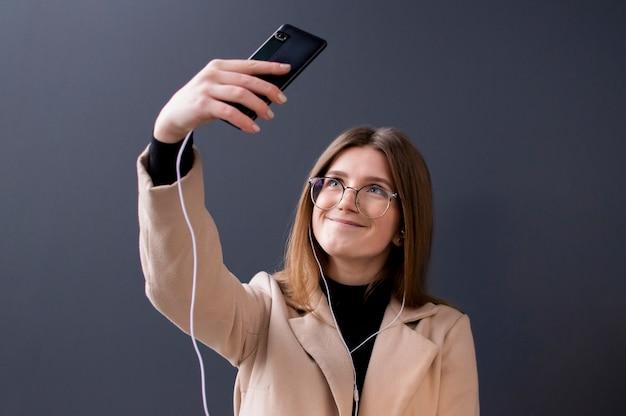 Młoda piękna dziewczyna w szkłach bierze selfie