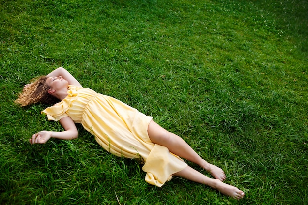Młoda piękna dziewczyna w żółtej sukience leży na trawie.