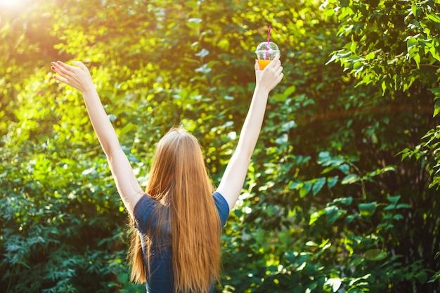 Młoda piękna dziewczyna wyciąga ręce do słońca, trzymając w ręku sok.