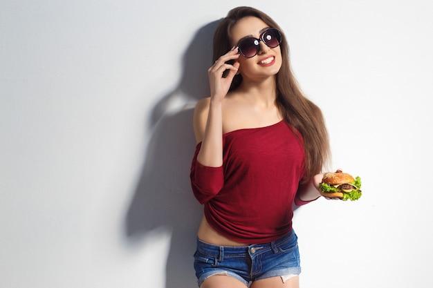 Młoda piękna dziewczyna z burger w jej ręce. studio strzał. model. posiłek typu fast food. dziewczyna ubrana w szorty i koszulkę, okulary przeciwsłoneczne na twarzy. pojęcie jedzenia.
