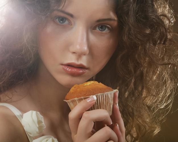 Młoda piękna dziewczyna z ciastem, szczęśliwy czas