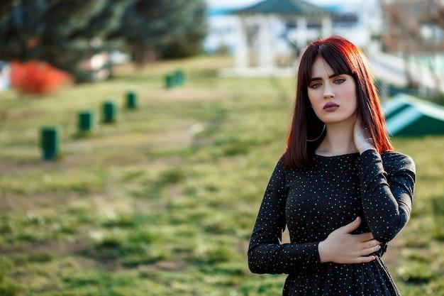 Młoda piękna dziewczyna z ciężkim i ponurym spojrzeniem w czerni sukni na zewnątrz pozować podczas zmierzchu