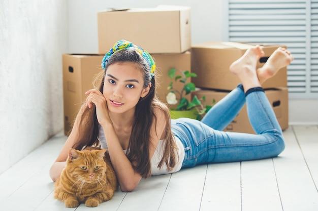 Młoda piękna dziewczyna z czerwonym kotem i pudełkami do ruchu