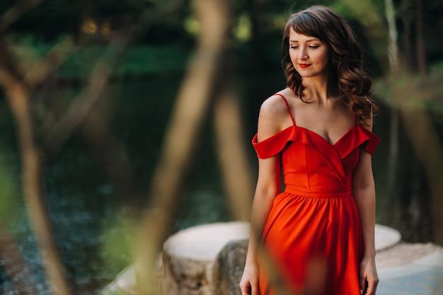 Młoda piękna dziewczyna z długimi brązowymi włosami, w długiej czerwonej sukience z pierścieniem wokół jeziora.