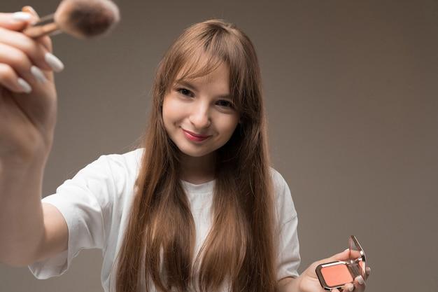 Młoda piękna dziewczyna z długimi falującymi włosami w stylu rustykalnym, makijażem nud, ubrana w białą dżersej, trzyma pędzel do makijażu i róż