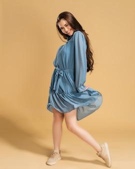 Młoda piękna dziewczyna z długimi kręconymi włosami trzyma krawędź niebieskiej letniej sukienki na pastelowej pomarańczy.