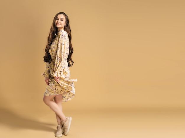 Młoda piękna dziewczyna z długimi kręconymi włosami w letniej sukience pozowanie na pastelowy pomarańczowy.