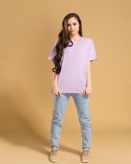 Młoda piękna dziewczyna z długimi kręconymi włosami w liliowej koszulce i dżinsach na pastelowej pomarańczy.
