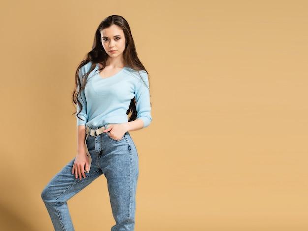 Młoda piękna dziewczyna z długimi kręconymi włosami w niebieskiej bluzie i dżinsach na pastelowej pomarańczy. makieta bluzy.