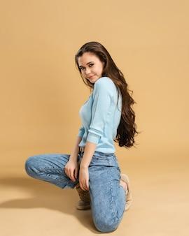 Młoda piękna dziewczyna z długimi kręconymi włosami w niebieskiej bluzie i dżinsach stoi na jednym kolanie na pastelowej pomarańczy.