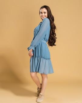 Młoda piękna dziewczyna z długimi kręconymi włosami w niebieskiej letniej sukience na pastelowy pomarańczowy.