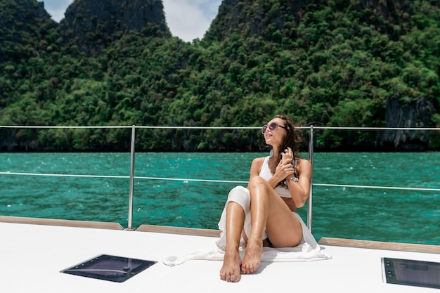 Młoda piękna dziewczyna z długimi włosami siedzi na dziobie jachtu w białej spódnicy i bikini.