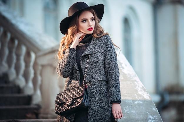 Młoda piękna dziewczyna z doskonałym makijażem, czerwonymi ustami, w czarnym kapeluszu i szarym płaszczu, czarna sukienka
