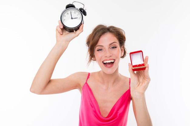 Młoda piękna dziewczyna z falistymi brązowymi łatami włosów, czystą skórą, płaskimi zębami, pięknym uśmiechem, w różowej koszulce, trzyma pudełko na pierścień treningowy i radzi, aby nie spieszyć się z małżeństwem