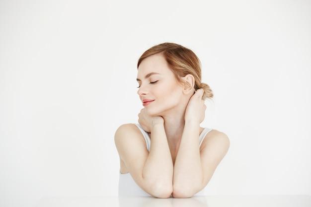 Młoda piękna dziewczyna z idealnie czystą skórą, uśmiechając się z zamkniętymi oczami siedząc przy stole. beauty spa i kosmetologia.