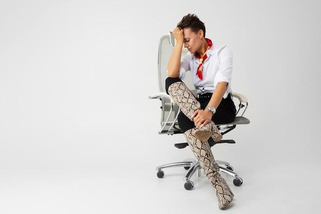 Młoda piękna dziewczyna z krótkimi ciemnymi włosami, makijażem w białej koszuli, czarnymi spodniami, długimi skórzanymi wężowymi butami, z czerwonym szalikiem, zegarkiem i pięknym makijażem siedzi na białym krześle komputerowym i myśli