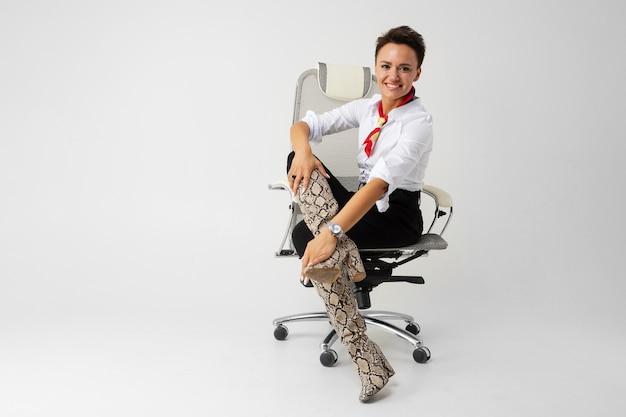 Młoda piękna dziewczyna z krótkimi ciemnymi włosami, makijażem w białej koszuli, czarnymi spodniami, długimi skórzanymi wężowymi butami, z czerwonym szalikiem, zegarkiem i pięknym makijażem siedzi na białym krześle komputerowym i uśmiecha się