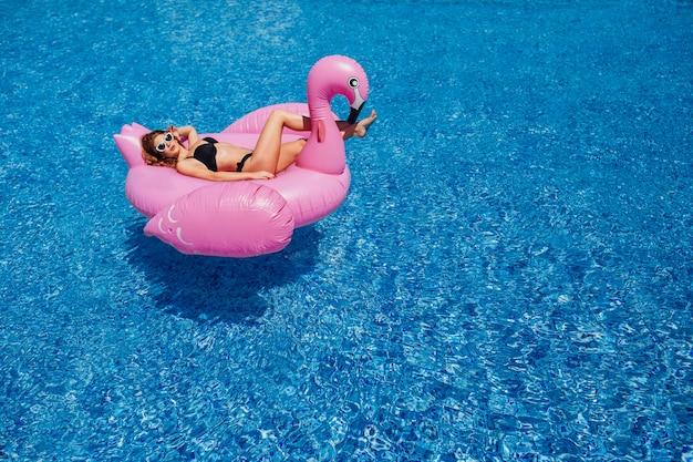 Młoda piękna dziewczyna z piękną postacią w czarnym kostiumu kąpielowym i okularach przeciwsłonecznych