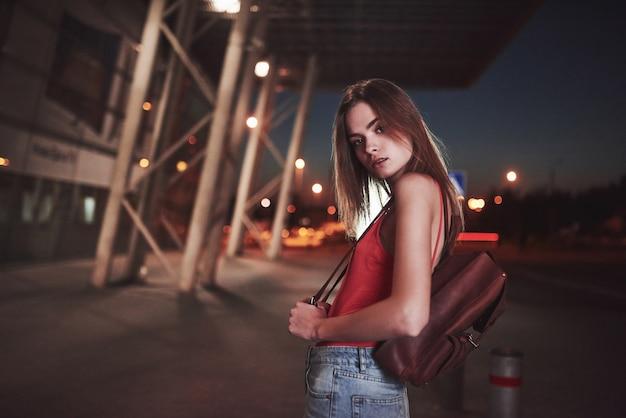 Młoda piękna dziewczyna z plecakiem za plecami stoi na ulicy w pobliżu lotniska