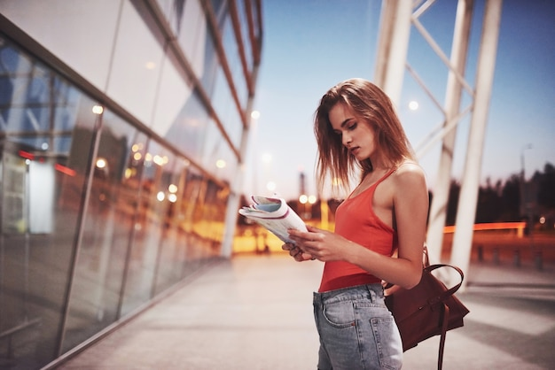 Młoda piękna dziewczyna z plecakiem za ramionami, stojąca na ulicy w pobliżu lotniska. właśnie przyjechała z reszty i bardzo szczęśliwa!